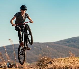 Jugendlicher macht einen Sprung mit einem Haibike SEET-HardFour Fahrrad